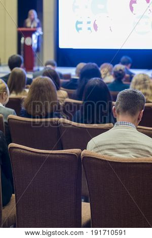 Business Conferences and Ideas. Group of People Attending Conference and Listening to the Host Speaker On Stage. Back View. Vertical Image Composition