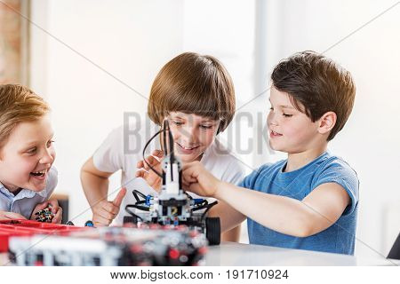 Everything is done. Busy happy boys are creating robot. They working in workshop