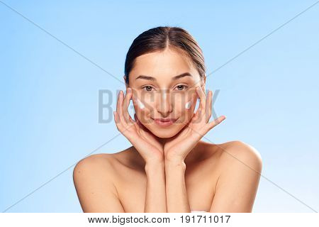 Woman with cream on blue background portrait.