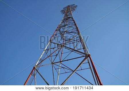 high television antenna on a background of the blue sky. tallest structure with electricity