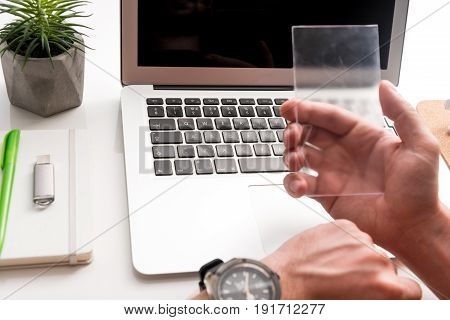 Innovative device. Close up of transparent smartphone being in hand of businessman. Focus on laptop on the background. Future technology concept