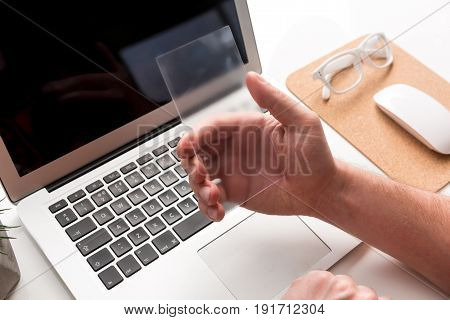 Technological advances. Close up of sophisticated modern smartphone being in hands of young man. Laptop and office suppliers on the background