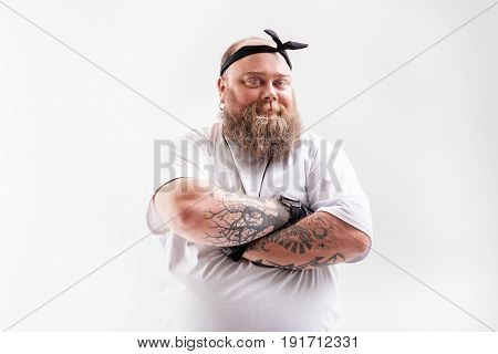 Waist up portrait of confident thick male hipster standing with crossed arms. He is smiling. Isolated