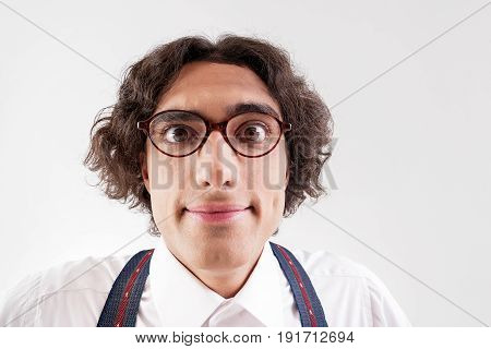 I need more knowledge. Portrait of cheerful young clever man with glasses staring at camera with interest. Isolated