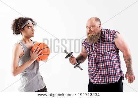 Angry male fatso is threatening to weak guy while holding weight. Victim is holding ball and looking at hipster with dread. Isolated