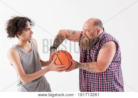 Bully fat male hipster is taking ball from weak boy. He is standing and grinning with aggression. Isolated