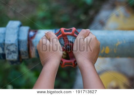 Children try to open the water valve.