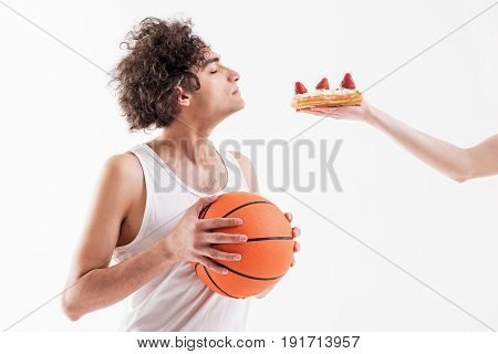 Hungry thin sportsman is smelling cake with cream and strawberry in female hand. His eyes are closed with temptation. Boy is standing and holding ball. Isolated