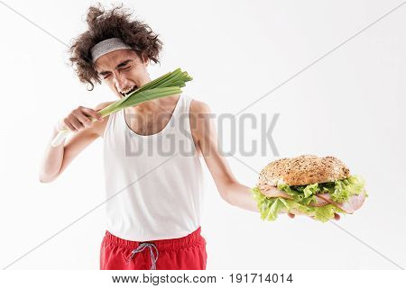 Hungry skinny guy is choosing to eat healthy food. He is biting vegetable with closed eyes while holding large appetite burger. Isolated