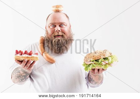 My favorite food. Portrait of glad bearded male fatso standing with donut on his head. He is carrying sausages on shoulder and holding cake and sandwich. Isolated