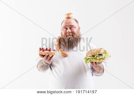 Happy fat man is holding unhealthy food and looking up with gratitude. He is standing and smiling. Isolated and copy space
