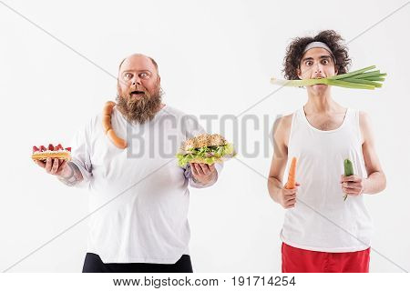 Obsessed of food. Excited fat man is holding sandwich with cake and sausages. Skinny boy is eating vegetables. They are standing and looking forward with shock