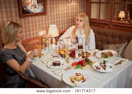 Two young blond women sit at table with meat dishes, fruit beverages and desserts.