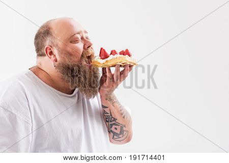 Hungry male fatso is eating sweet cake. His eyes are closed with enjoyment. Isolated and copy space in right side