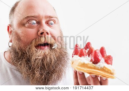 My precious. Portrait of excited male fatso looking at sweet cake with cream and strawberries. He is smiling with happiness. Isolated