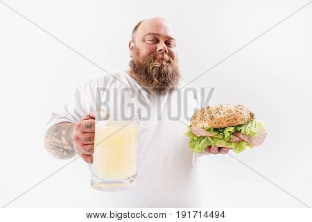 Cheers. Confident male fatso is stretching glass of cold beer to camera. He is showing big burger with meat and smiling. Isolated