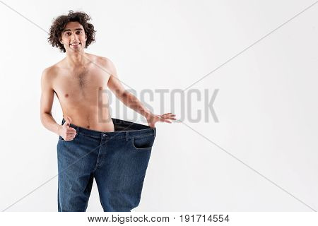 Look at my figure now. Happy young skinny guy is showing ok sign while stretching his pants sideways. He is standing and laughing. Isolated and copy space in right side