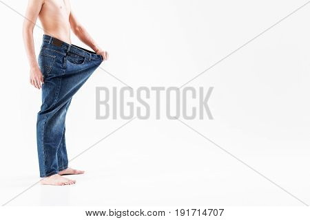 Close-up side view of young skinny man presenting result of diet. He is wearing big trousers and showing his weight loss. Isolated and copy space in right side