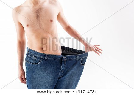 Close up of slim body of young man standing and stretching jeans sideways. He lost weight in twice. Isolated and copy space