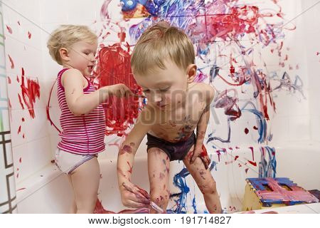 Portrait of two cute adorable white Caucasian little boy and girl playing painting on walls in bathroom having fun lifestyle active childhood concept early education development