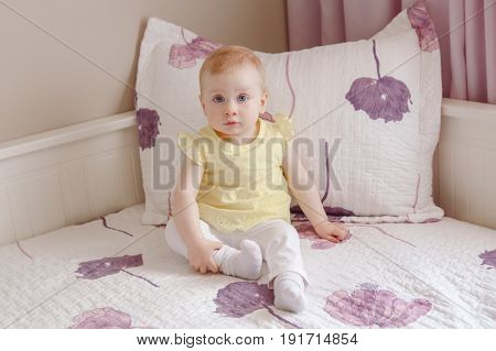 Portrait of cute adorable white blonde Caucasian smiling baby girl with large blue eyes in yellow shirt sitting on bed looking in camera