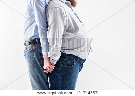 Love comes to everyone. Close up of bodies of loving homosexual couple holding hands while standing. Fat and slim men are leaning back on each other. Isolated and copy space