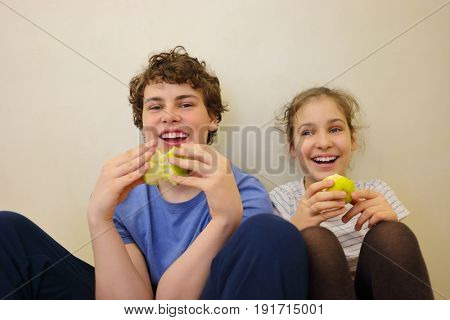 Happy brother and sister eat green apples and laugh near wall