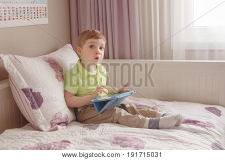 Portrait of cute adorable white Caucasian toddler boy sitting in bed playing with digital tablet with funny face expression candid lifestyle early development new technology generation