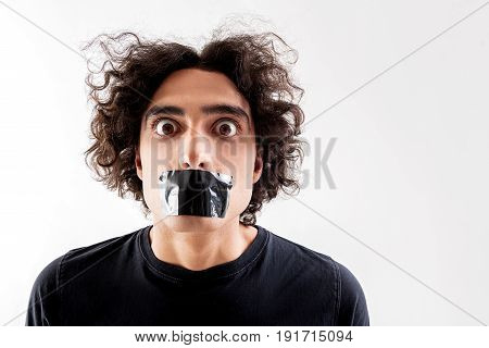 Keep silence. Portrait of shocked young man standing with gagged mouth by black by adhesive tape. He is looking at camera with fear. Isolated and copy space