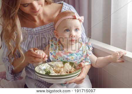 Closeup portrait of young woman mother trying to feed her baby girl daughter with vegetables broccoli cauliflower healthy organic food for child candid lifestyle family life