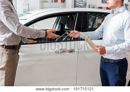 This is your automobile key. Serene worker giving tool to buyer. They standing near vehicle