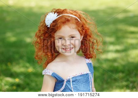 Closeup portrait of cute adorable little red-haired Caucasian girl child in blue dress standing in field meadow park outside looking in camera happy lifestyle childhood concept