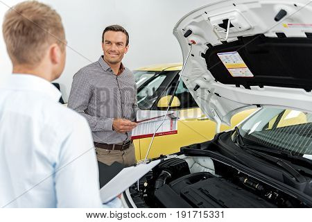 Happy male talking with salesman while looking through article about vehicle in automobile showroom