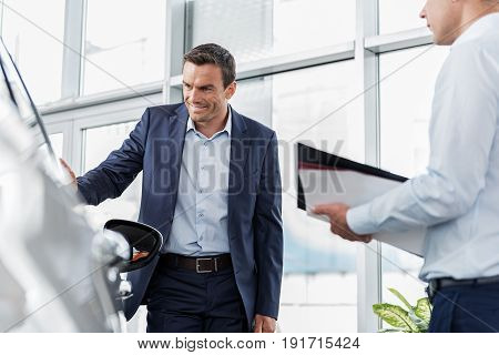 Low angle male demonstrating happiness while looking at modern car. He situating near it and telling with salesman in dealership