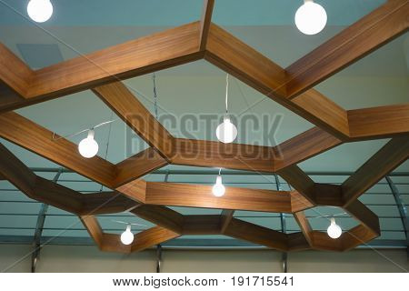 Ceiling with hanging wood and lightbulbs in restaurant, under view