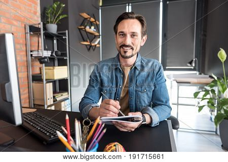 Cheerful man is holding notebook and ready to make notes. He glancing at camera with polite smile. Portrait