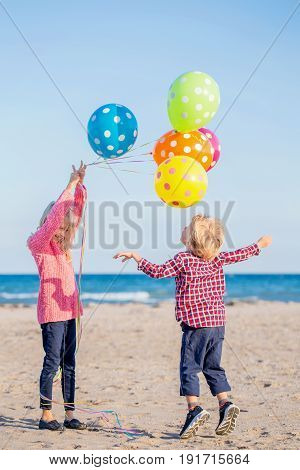 Group portrait of two funny white Caucasian children kids with colorful bunch of balloons playing running on beach on sunset happy lifestyle childhood concept