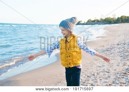 Portrait of smiling blonde white Caucasian child kid girl with long hair wearing yellow jacket gilet and grey hat on sea shore sand beach at sunset looking away happy lifestyle childhood