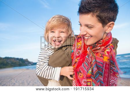 Group portrait of smiling white Caucasian mother and daughter baby girl piggy back riding playing running on ocean sea beach at sunset outdoors happy lifestyle childhood concept