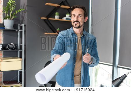 Cheerful manager is offering his ready made project. He keeping sheet of paper and glancing at camera with affable smile. Portrait