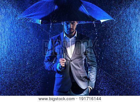 Handsome man walking with an umbrella on city street