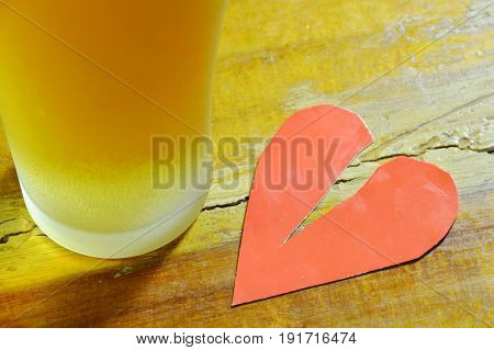 broken heart and glass of beer to forget on table