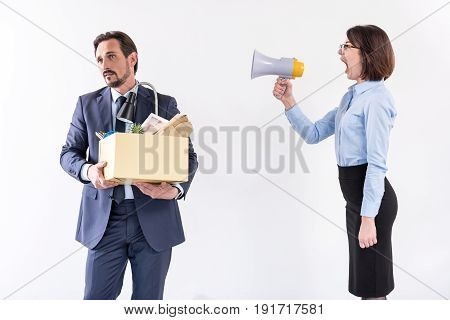 You are fired. Angry business woman is screaming through megaphone on frustrated dismissed employee with box of his belongings. Isolated background