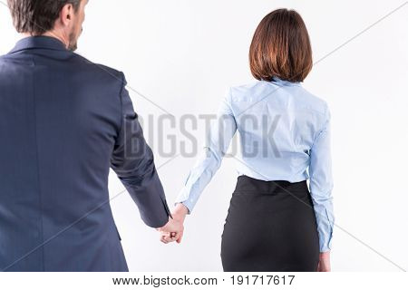 Follow me. Back view of mature man in suit is holding hand of young business woman. Isolated background
