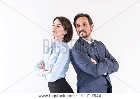 Pleasant collaboration. Portrait of smiling business colleagues are standing back to back with crossed arms. Isolated background
