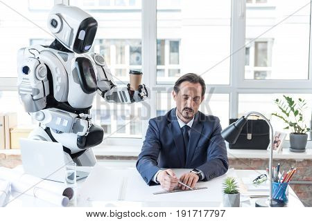 Busy at work. Caring robot is holding cup of coffee for senior manager, who is sitting at desk with laptop while doing mechanical drawing with concentration