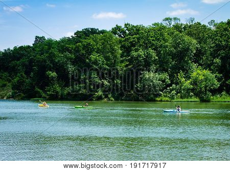 Three people kayaking on a lake in the park