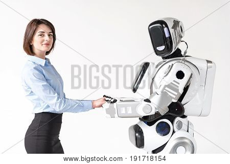 Sharing love. Positive charming girl is standing with modern android and holding his hands. They are looking at camera with gladness. Isolated background
