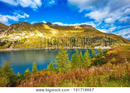 The concept of ecological tourism. Glacial lake with clear cold water. The harmony of the Dolomites. Mountain Lake Lago di Fedaia