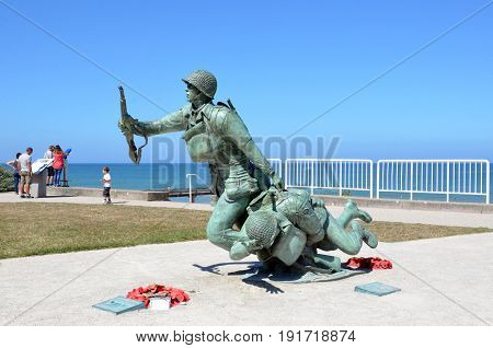 VIERVILLE-SUR-MER FRANCE - AUG 12: The 116th Regimental Combat Team Statue and Plaque is shown at Omaha Beach in Vierville-sur-Mer France on August 12 2016.